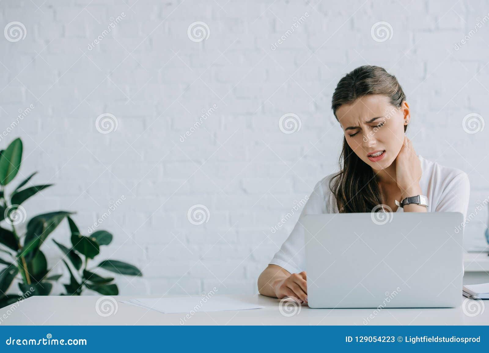 Jeune douleur de femme d affaires de douleur cervicale tout en travaillant