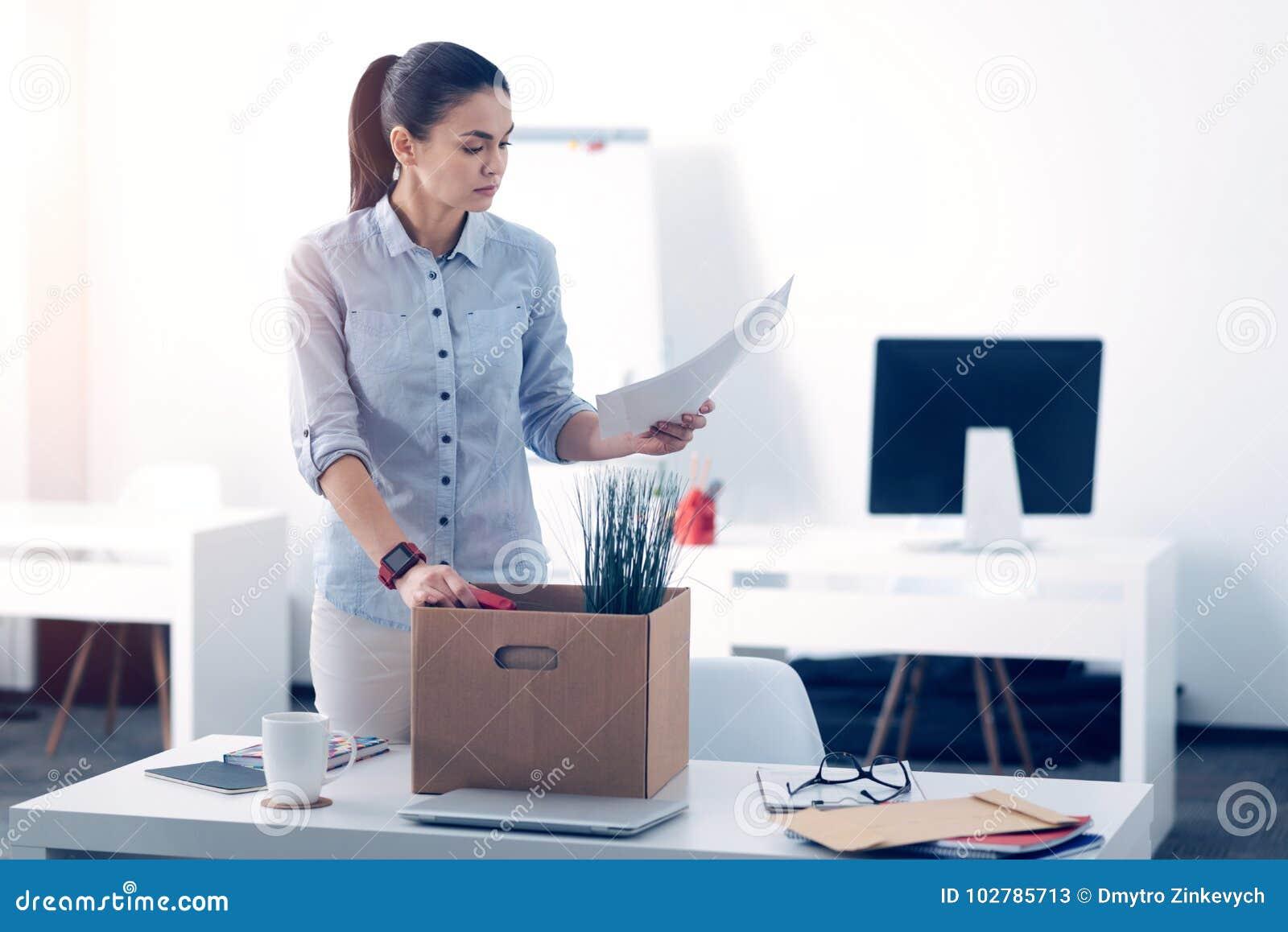 Jeune employé emballant sa substance dans la boîte tout en quittant le travail