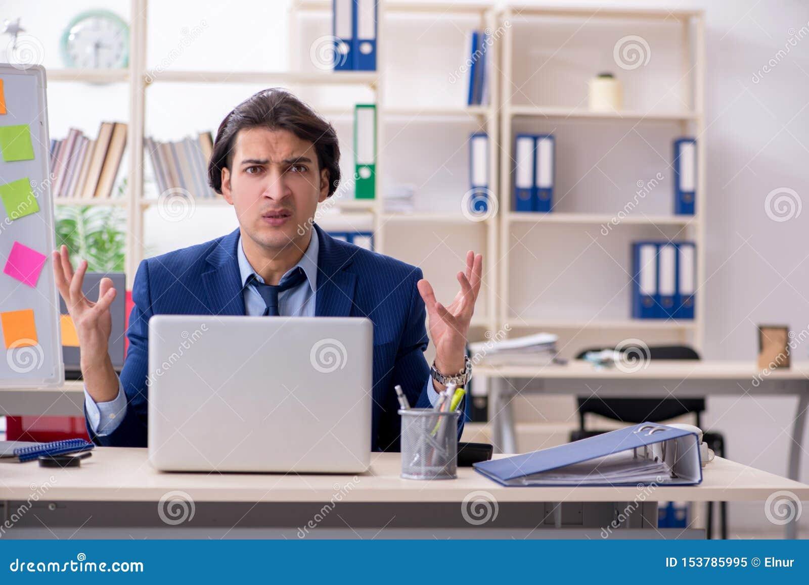 Jeune employ? masculin peu satisfait du travail excessif