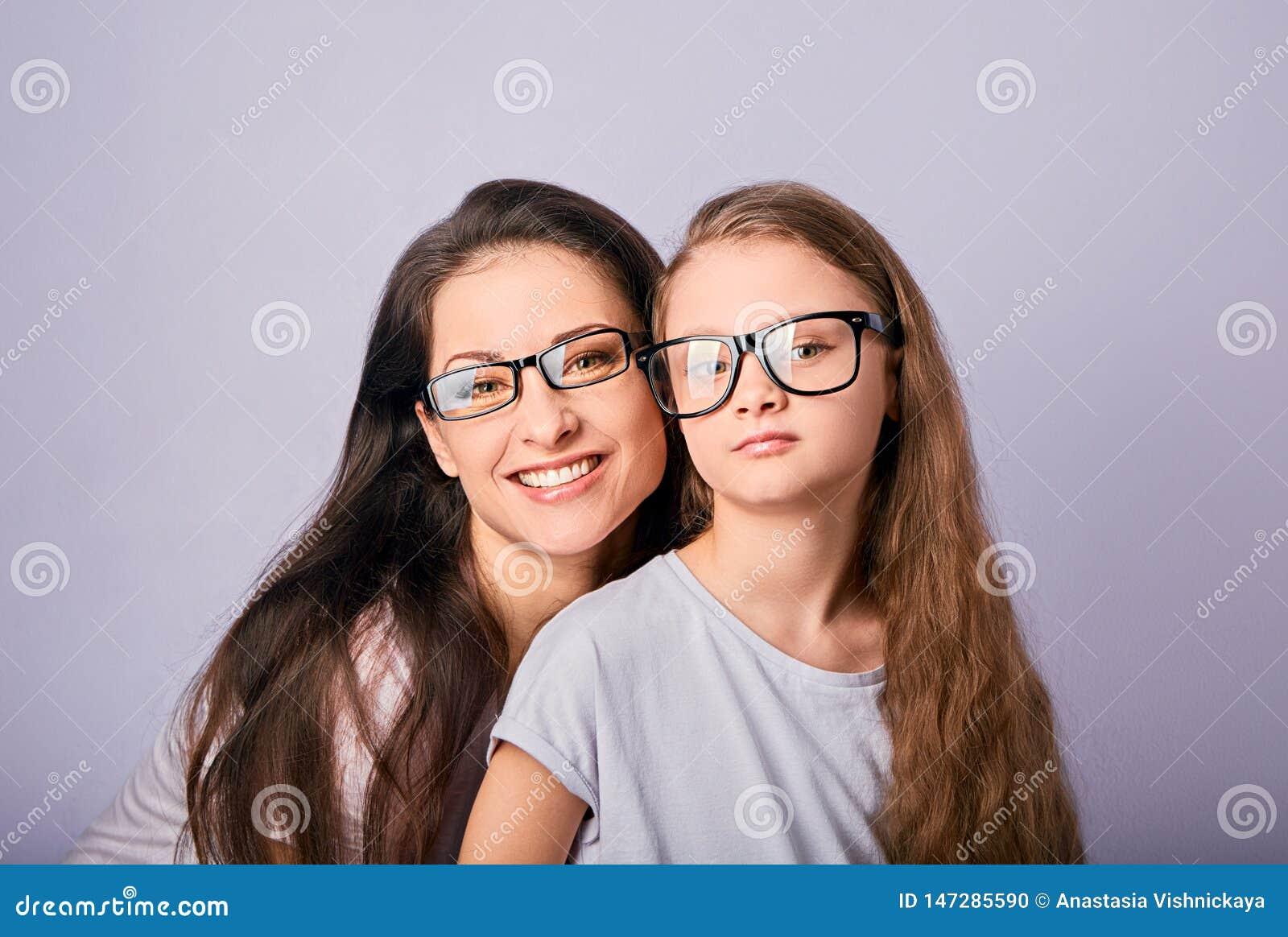 Jeune enfant occasionnel heureux de m?re et de sourire en verres de mode ?treignant sur le fond pourpre avec l espace vide de cop