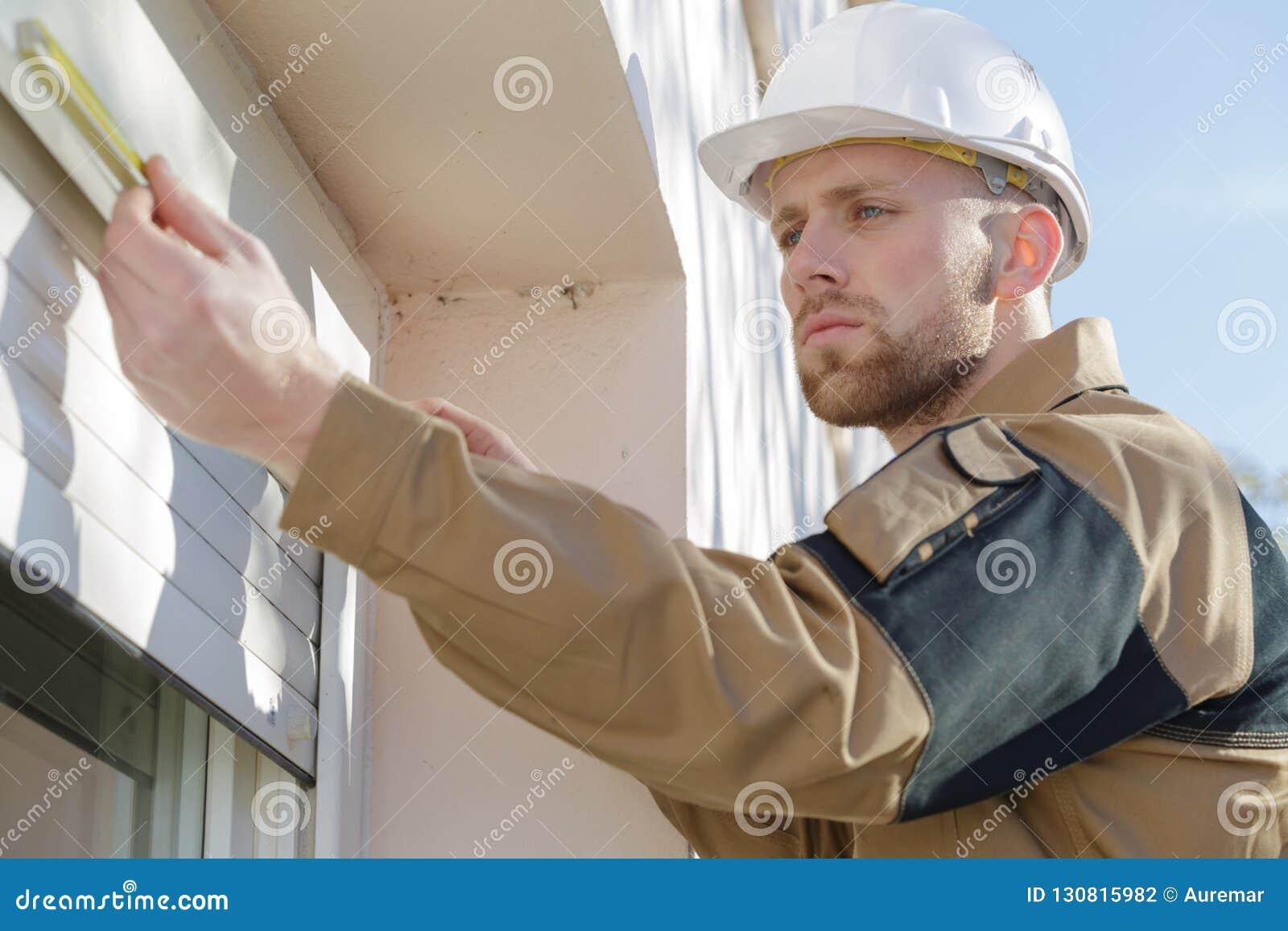Jeune entrepreneur installant des abat-jour de fenêtre