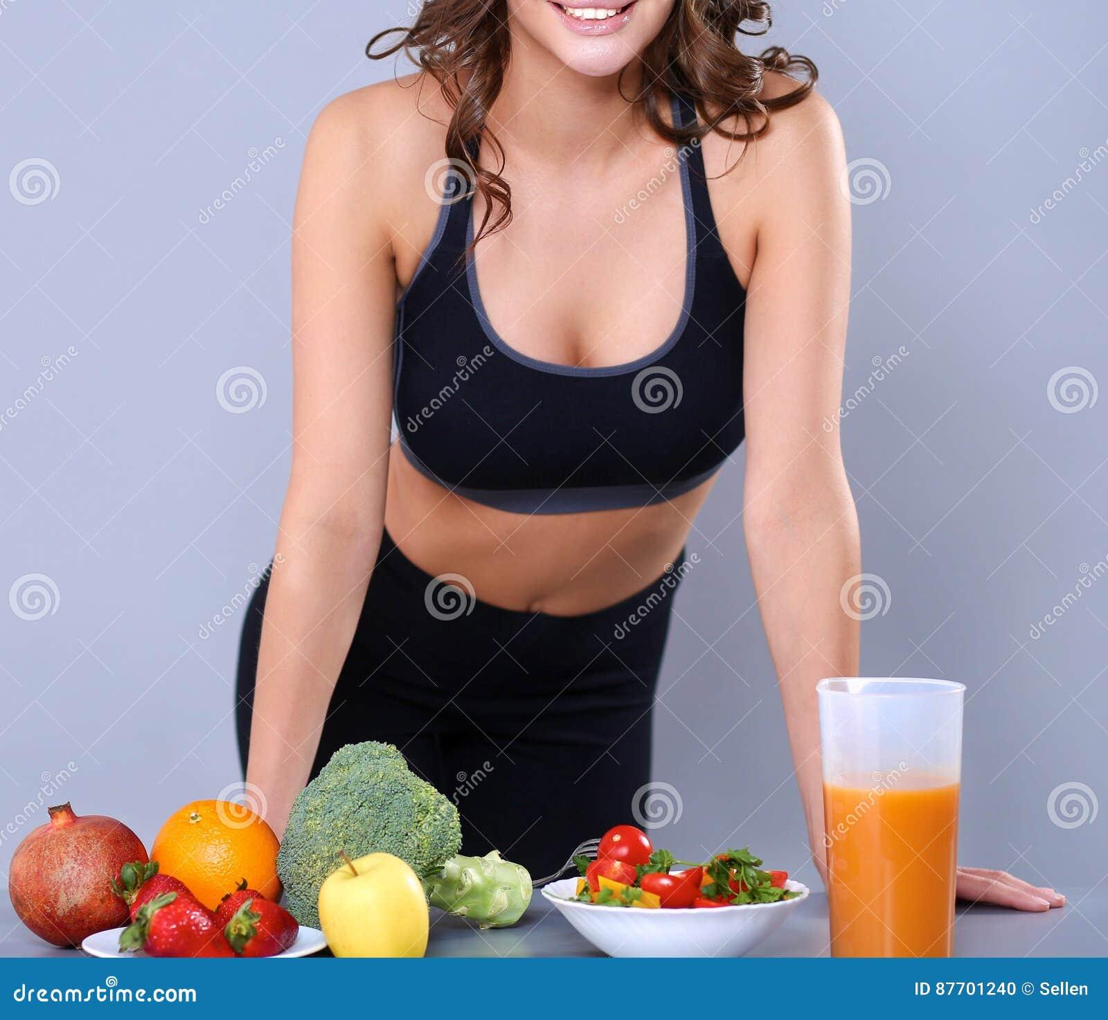 Jeune et belle femme tenant le bureau proche avec des légumes