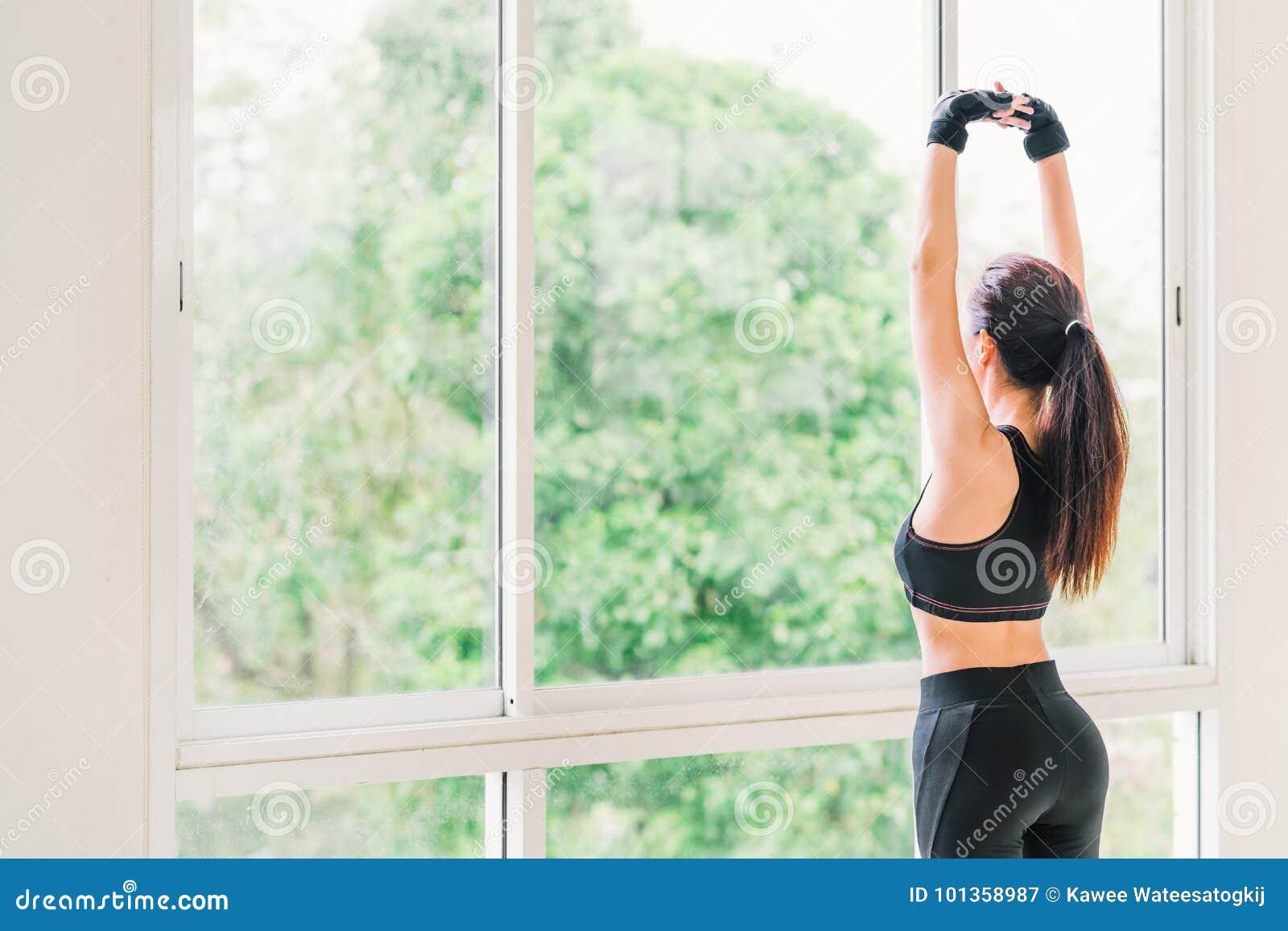 Jeune exercice de bras asiatique sexy de bout droit de fille au club de sport de forme physique ou au gymnase à la maison Classe