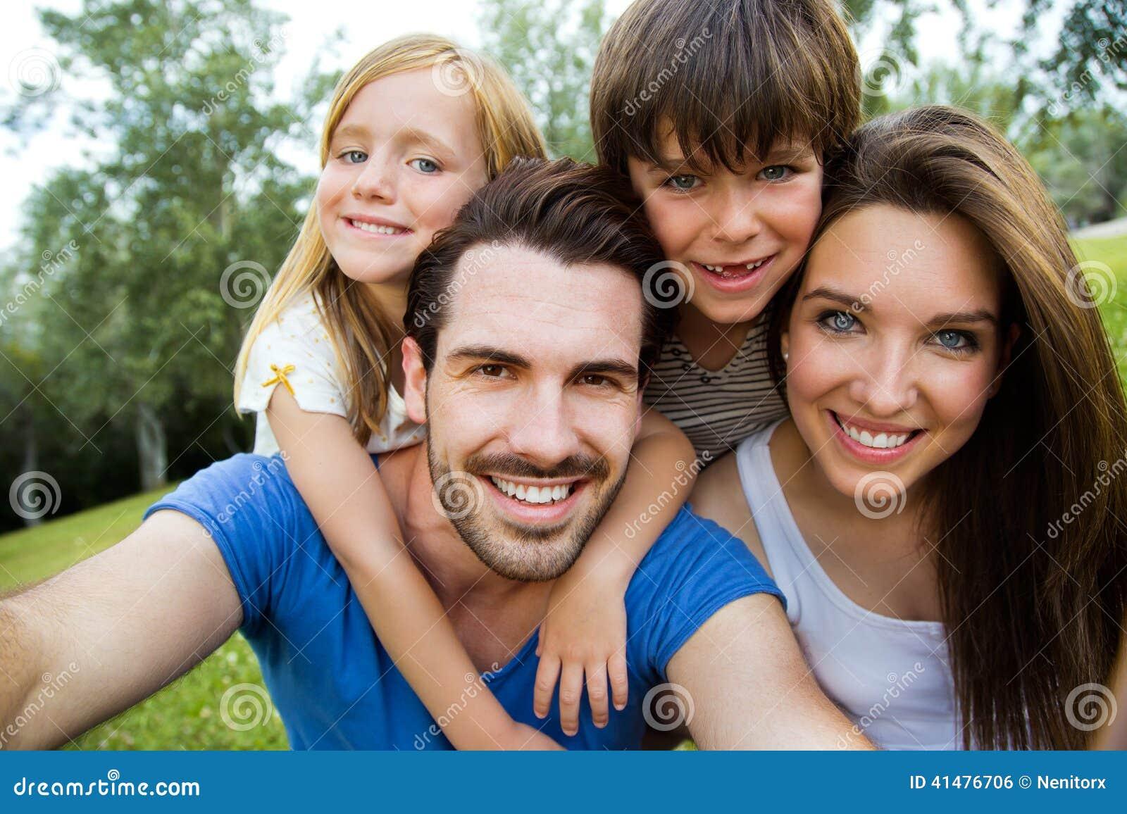Jeune famille heureuse prenant des selfies avec son smartphone dans le pair