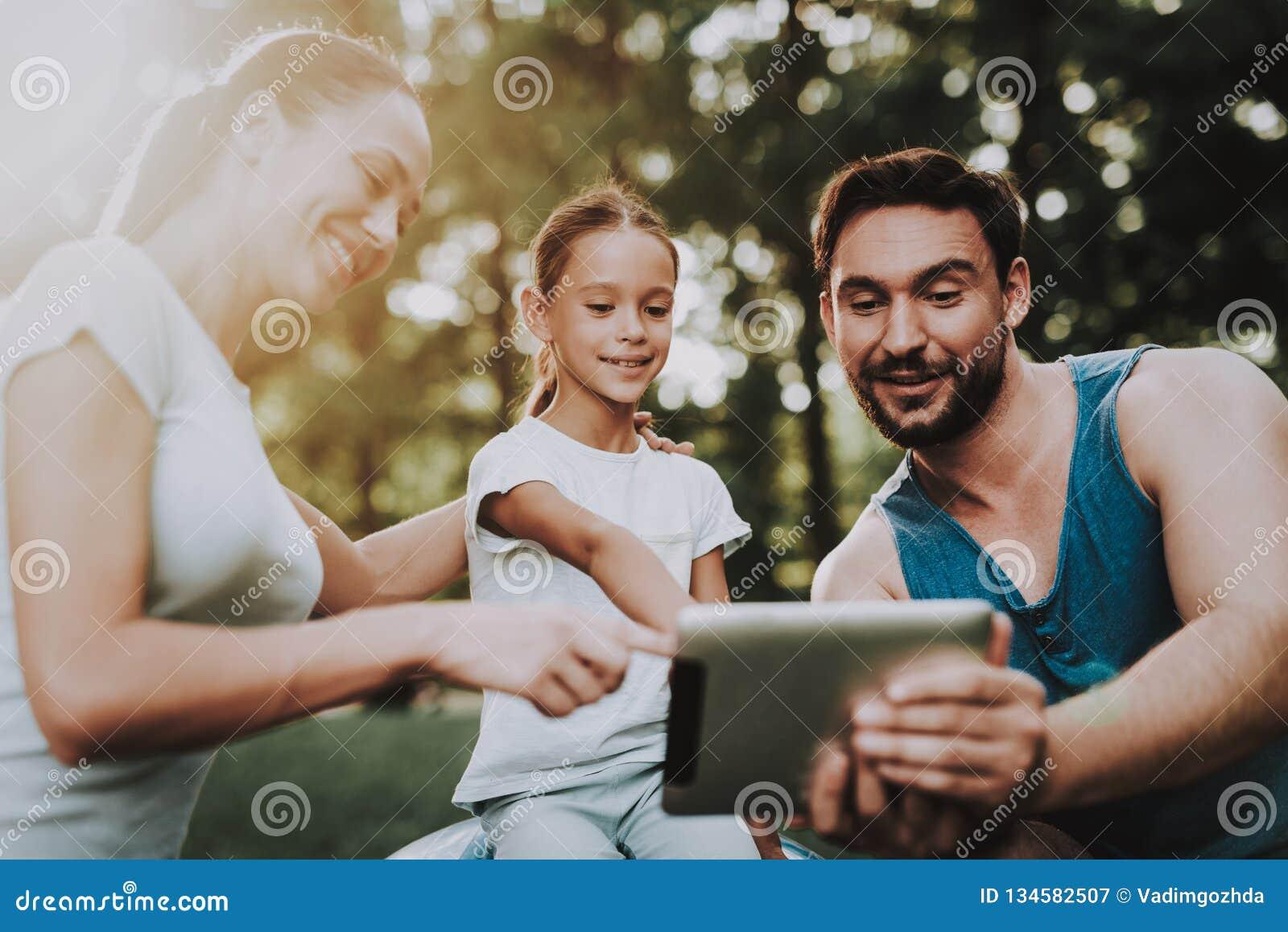 Jeune famille heureuse utilisant la Tablette en parc d été