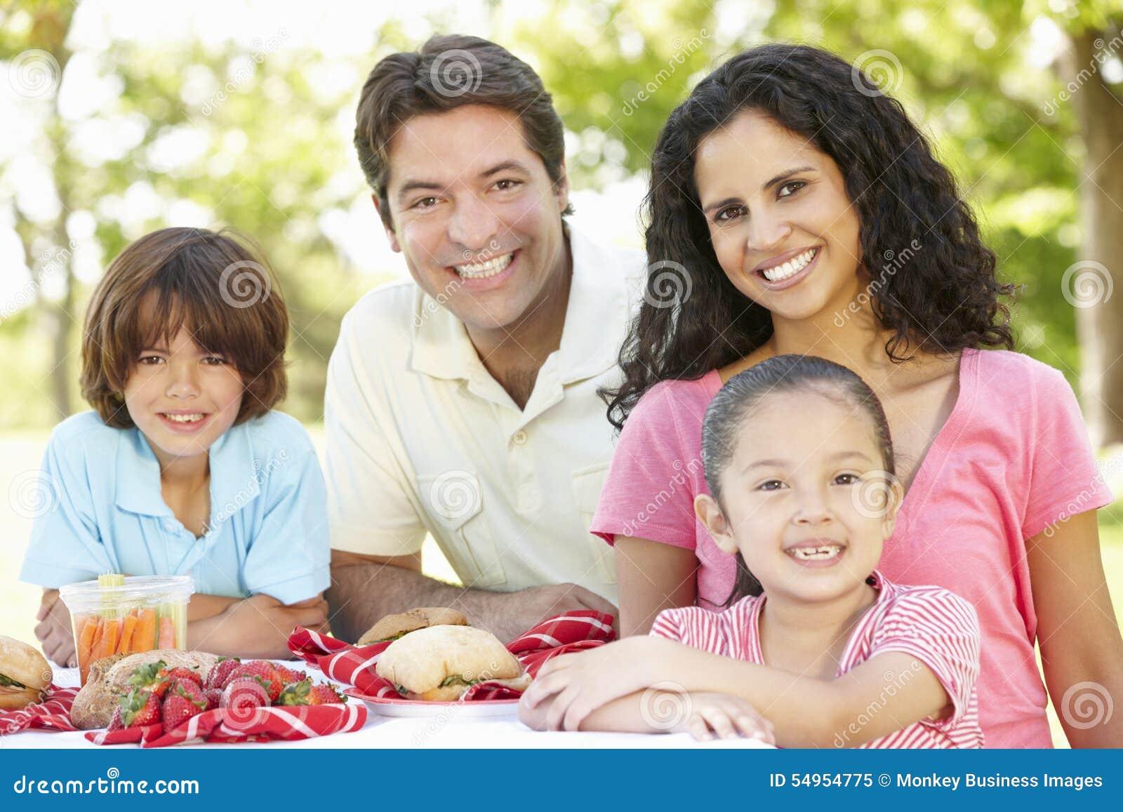 Jeune famille hispanique appréciant le pique-nique en parc