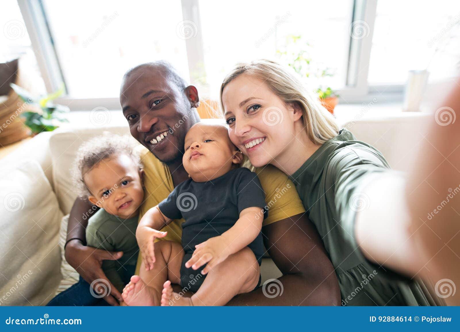 Jeune famille interraciale avec de petits enfants prenant le selfie