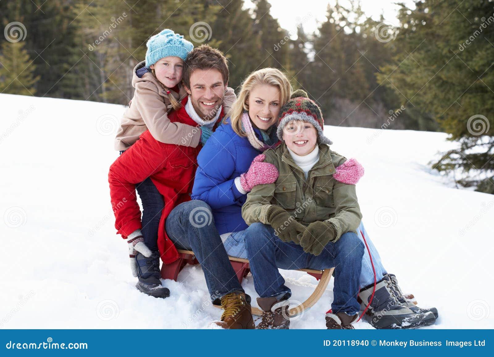Jeune famille s asseyant sur un traîneau dans la neige