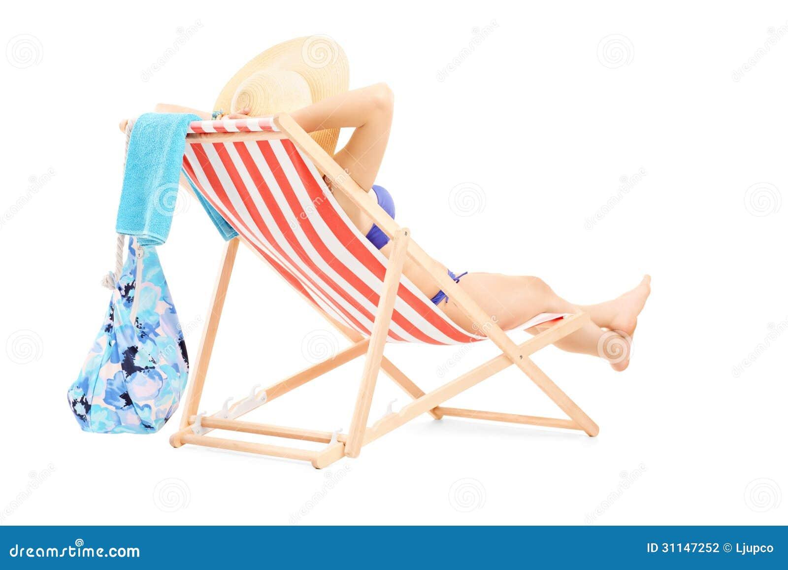 Jeune femelle dans le bikini se trouvant sur une chaise de plage