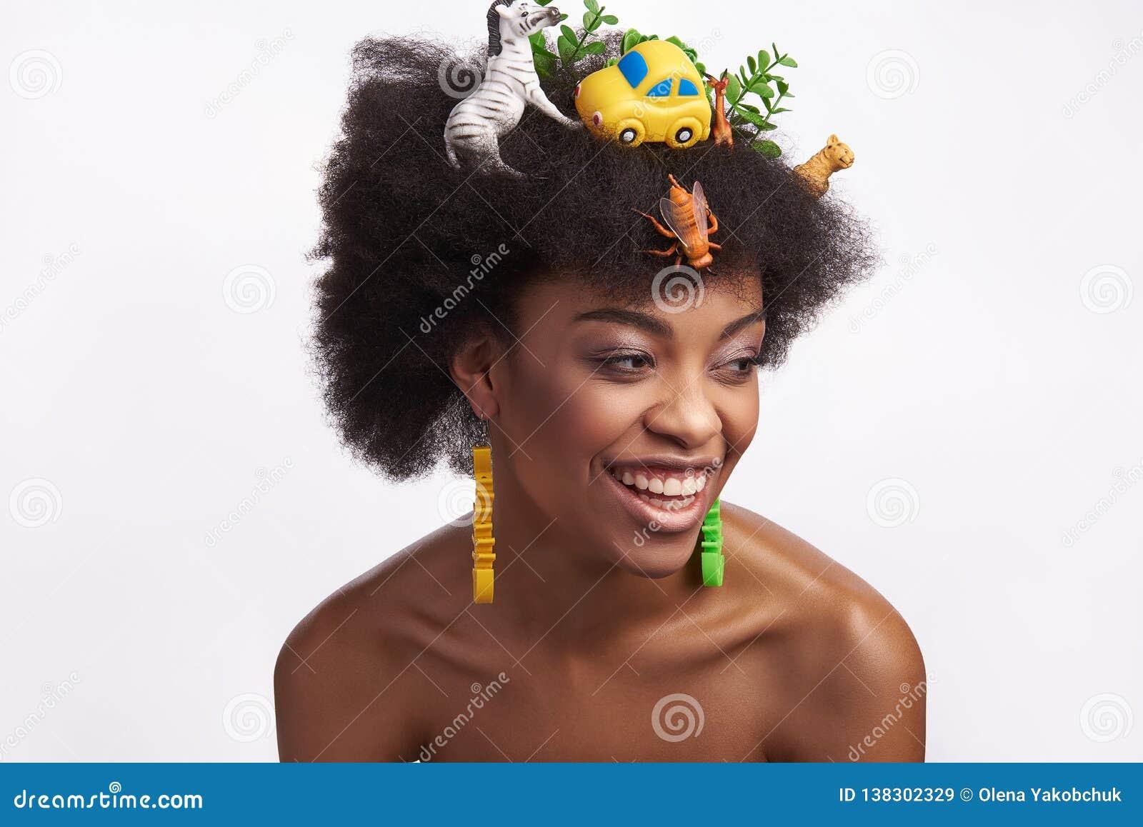 Jeune femelle ethnique riante dans la coiffure de safari