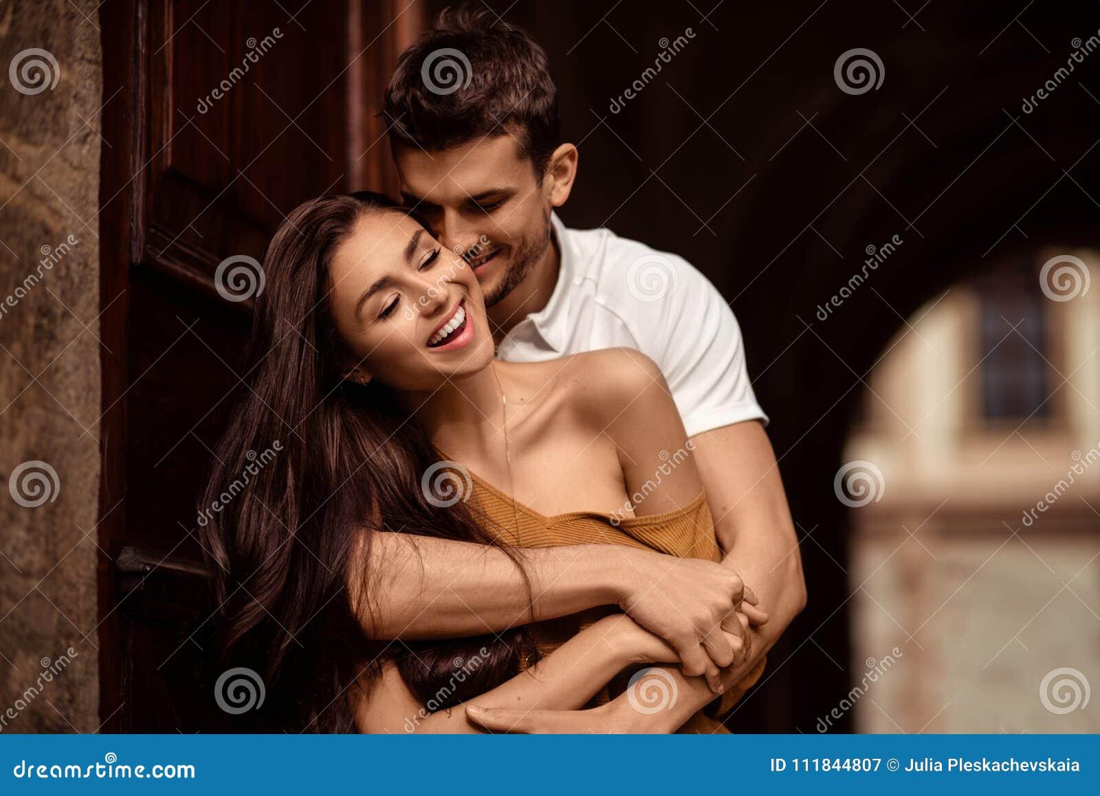 Jeune femelle heureuse avec de longs cheveux foncés heureux de recevoir le baiser passionné de son ami Le mâle beau embrasse le s