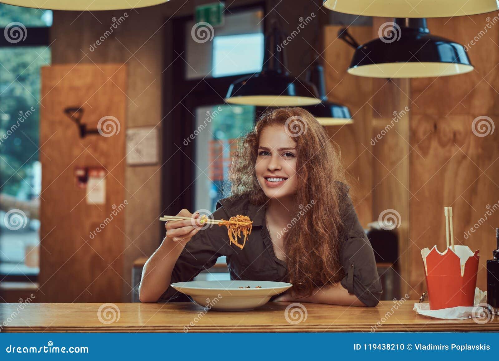 Jeune femelle rousse mangeant les nouilles épicées dans un restaurant asiatique