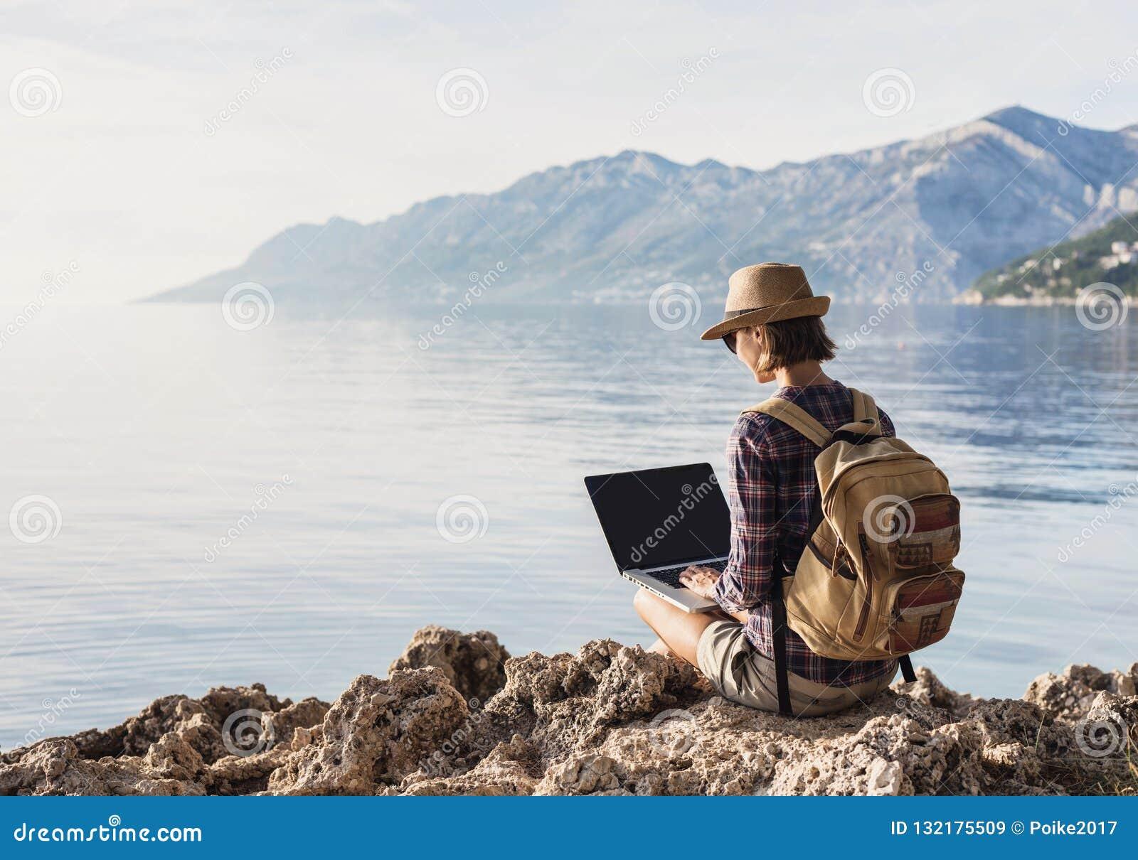 Jeune femme à l aide de l ordinateur portable sur une mer Travaillent en indépendants le concept de travail