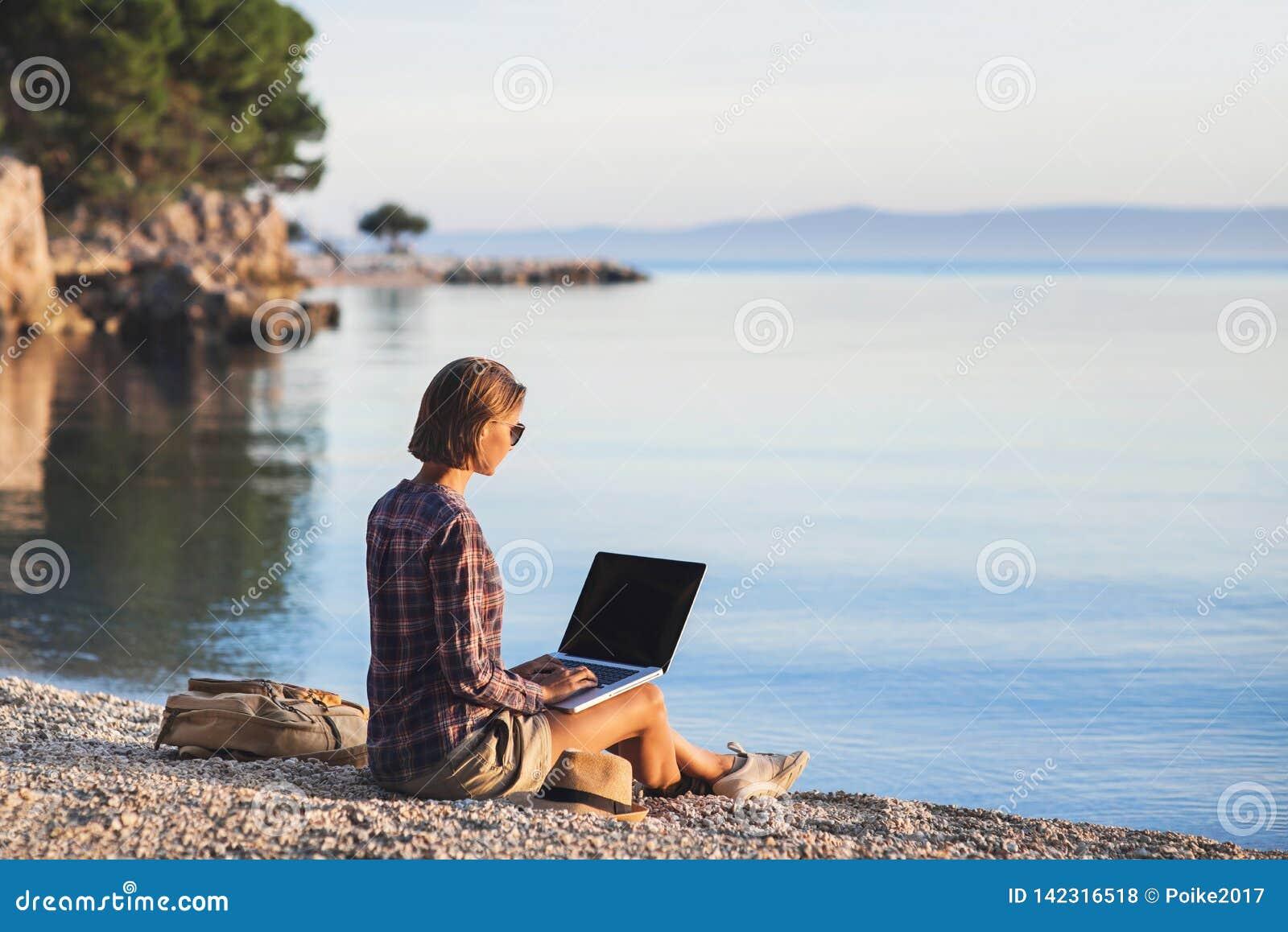 Jeune femme à l aide de l ordinateur portable sur une plage Travaillent en indépendants le concept de travail