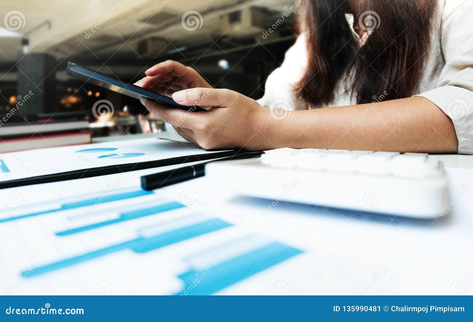 Jeune femme à l aide du comprimé tout en travaillant sur des documents de données