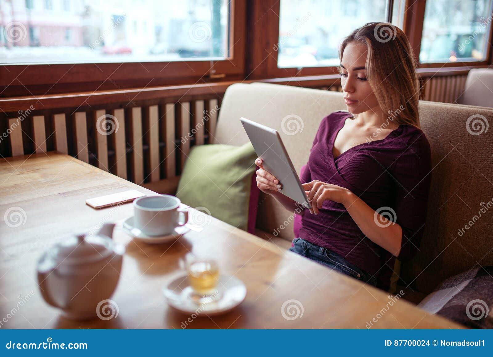 Jeune femme à l aide du PC de comprimé en café
