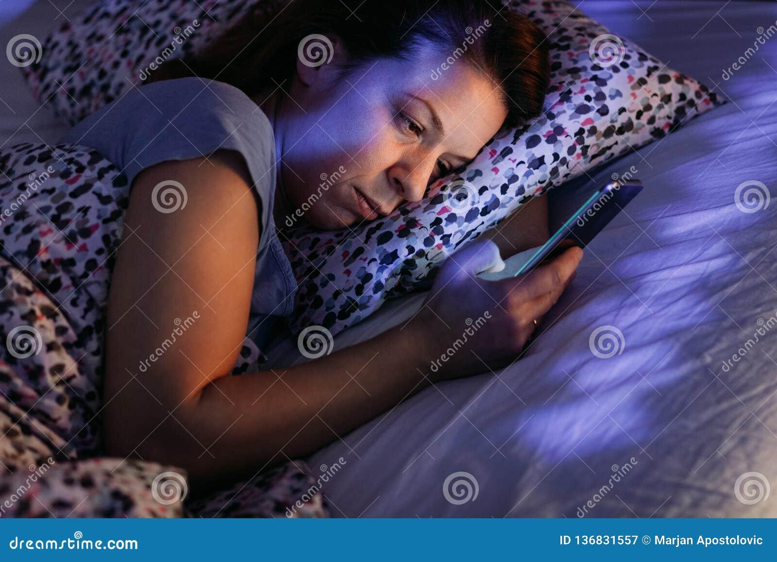 Jeune femme à l aide du smartphone dans le lit la nuit