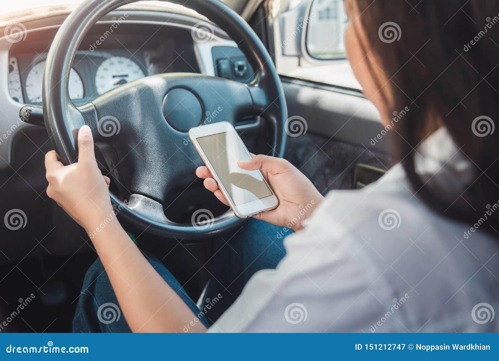 Jeune femme à l aide du téléphone intelligent tout en conduisant une voiture