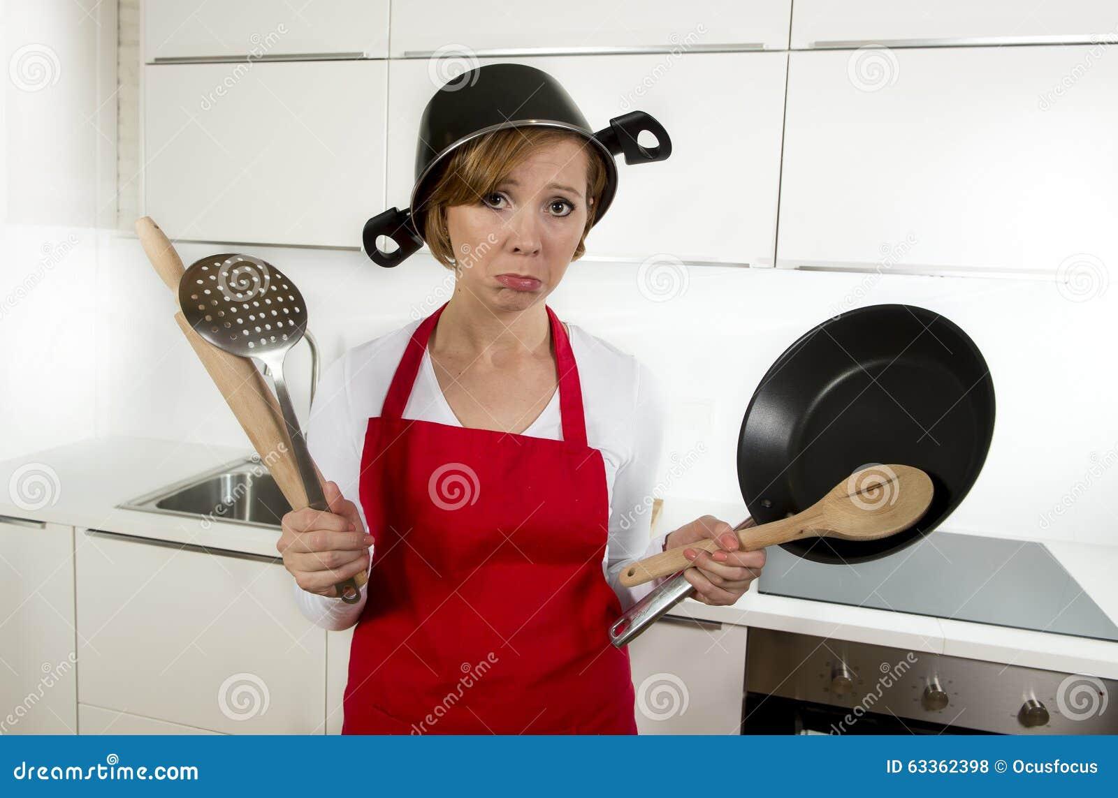 Jeune femme à la maison attirante de cuisinier dans le tablier rouge à la cuisine tenant la casserole et le ménage avec le pot su