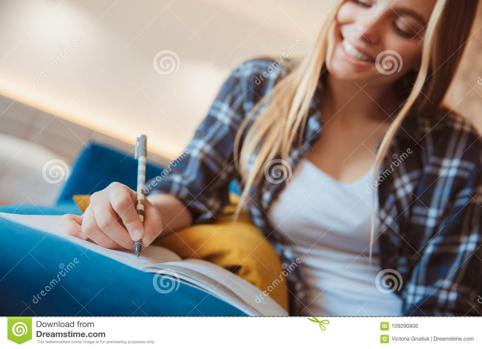 Jeune femme à la maison dans le salon prenant des notes en gros plan
