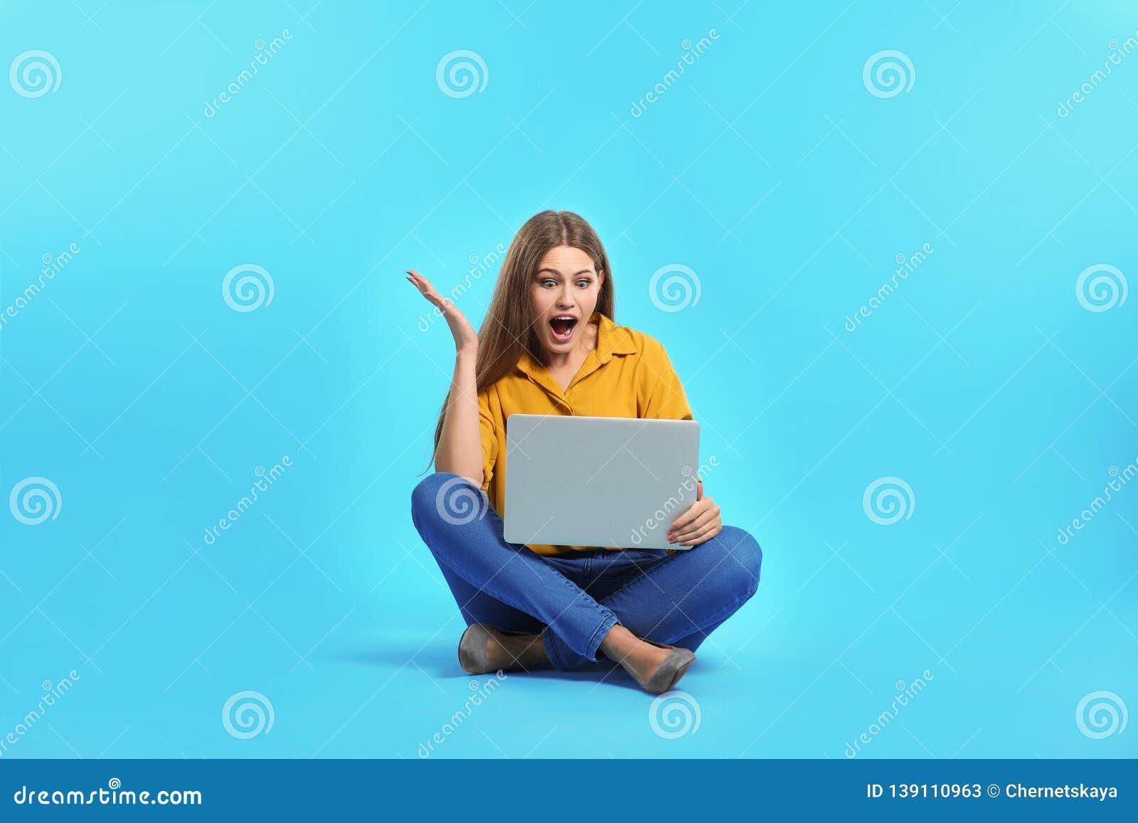 Jeune femme émotive avec l ordinateur portable célébrant la victoire