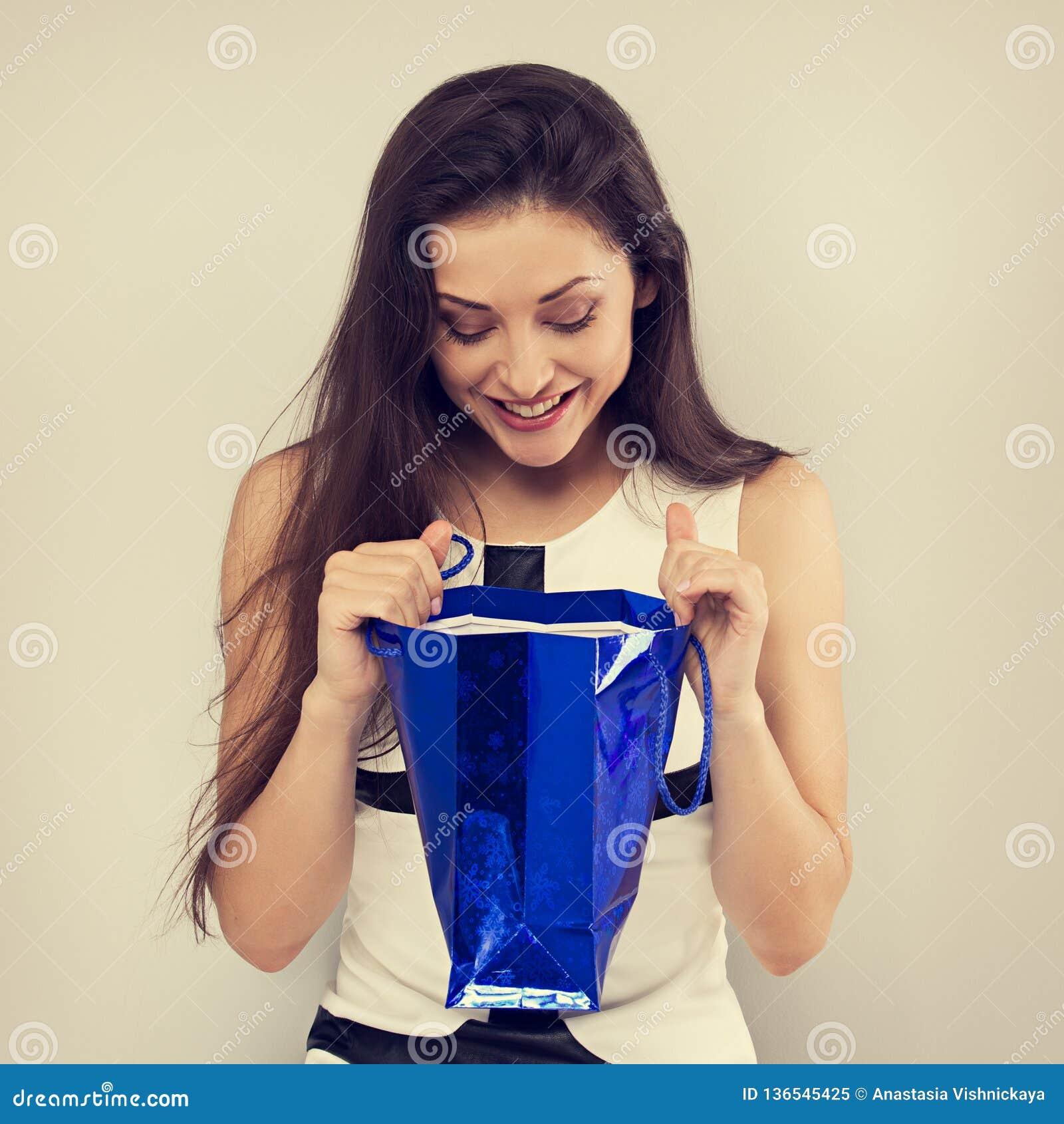 Jeune femme étonnante enthousiaste regardant dans le sac bleu de cadeau avec le sourire sur le fond bleu Bonnes fêtes