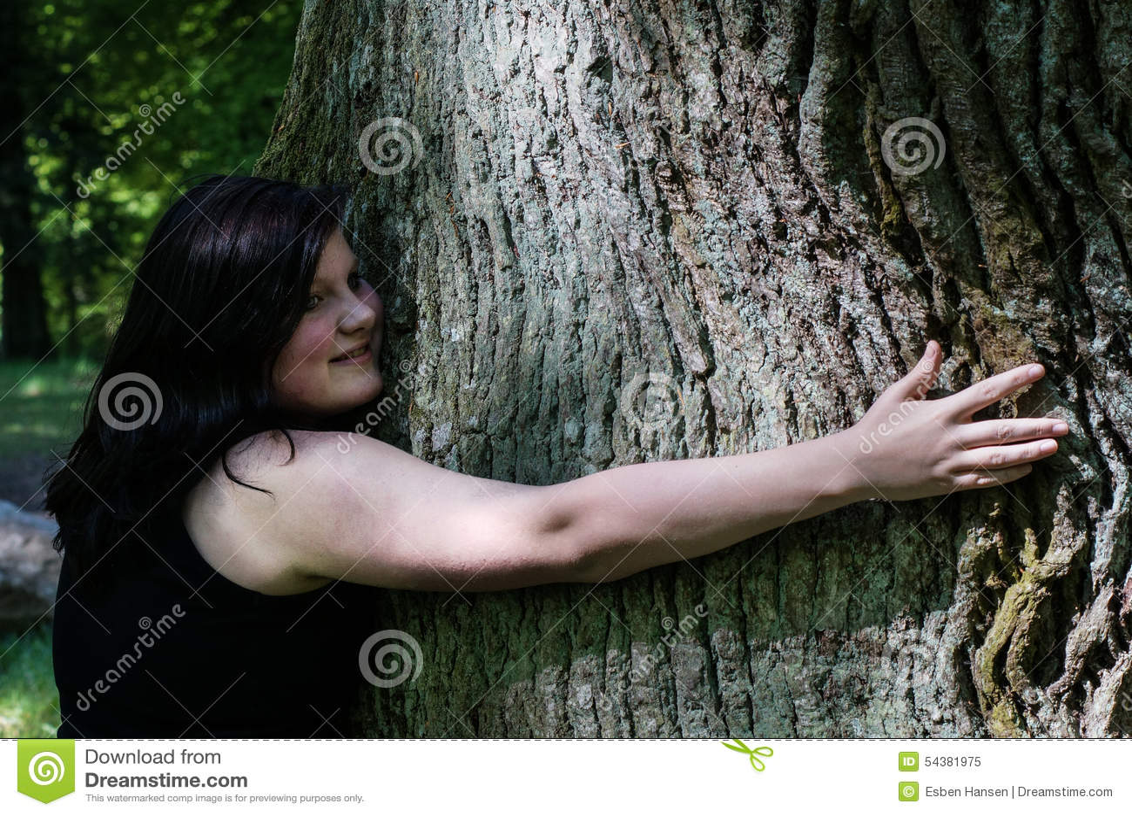 Jeune femme étreignant un arbre