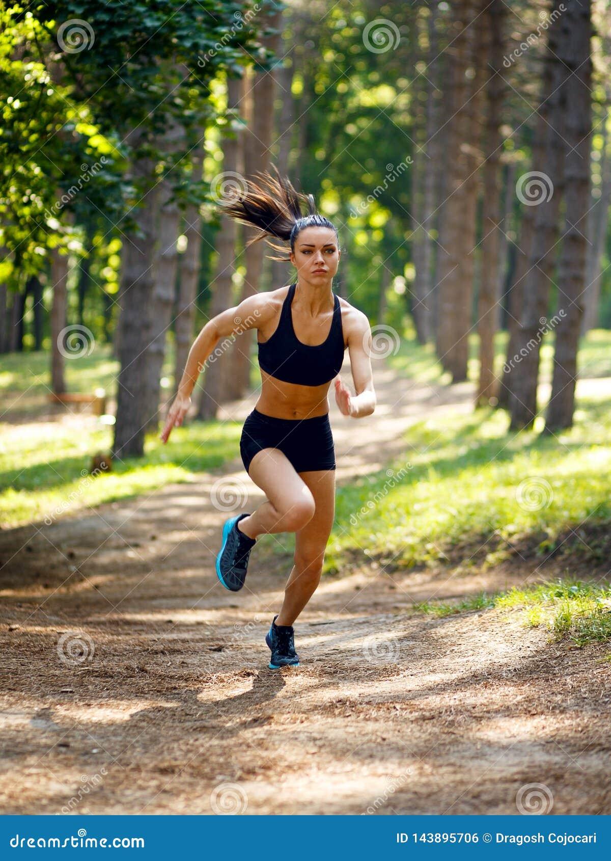 Jeune femme active de brune courant en parc, été, corps sain et parfait de ton Séance d entraînement dehors Concept de mode de vi