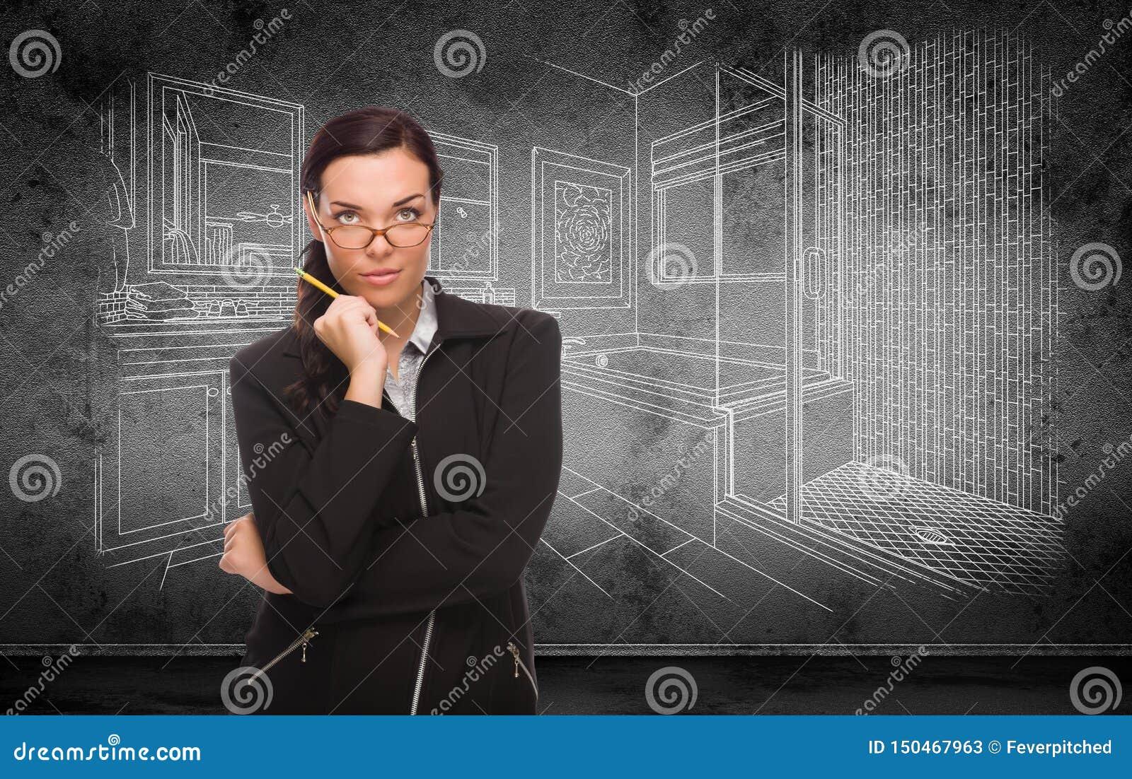 Jeune femme adulte avec le crayon devant le dessin d étude de salle de bains sur le mur