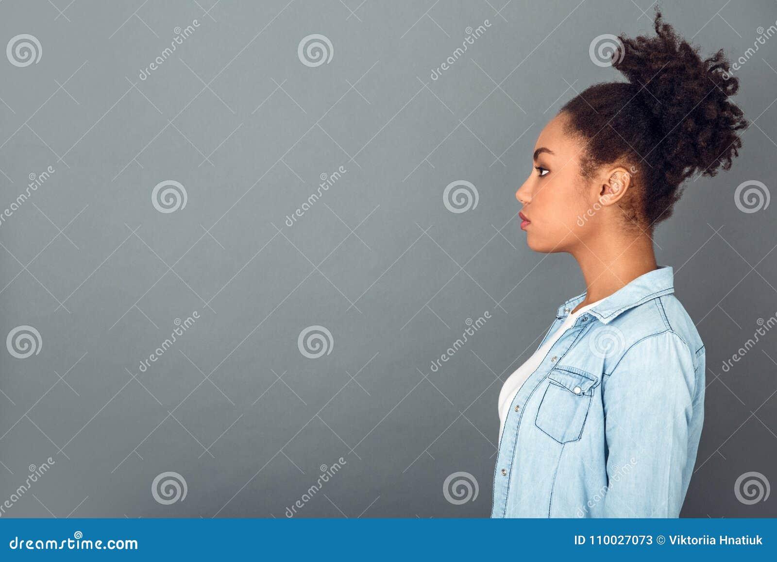 Jeune femme africaine d isolement sur le profil quotidien occasionnel de mode de vie de studio gris de mur