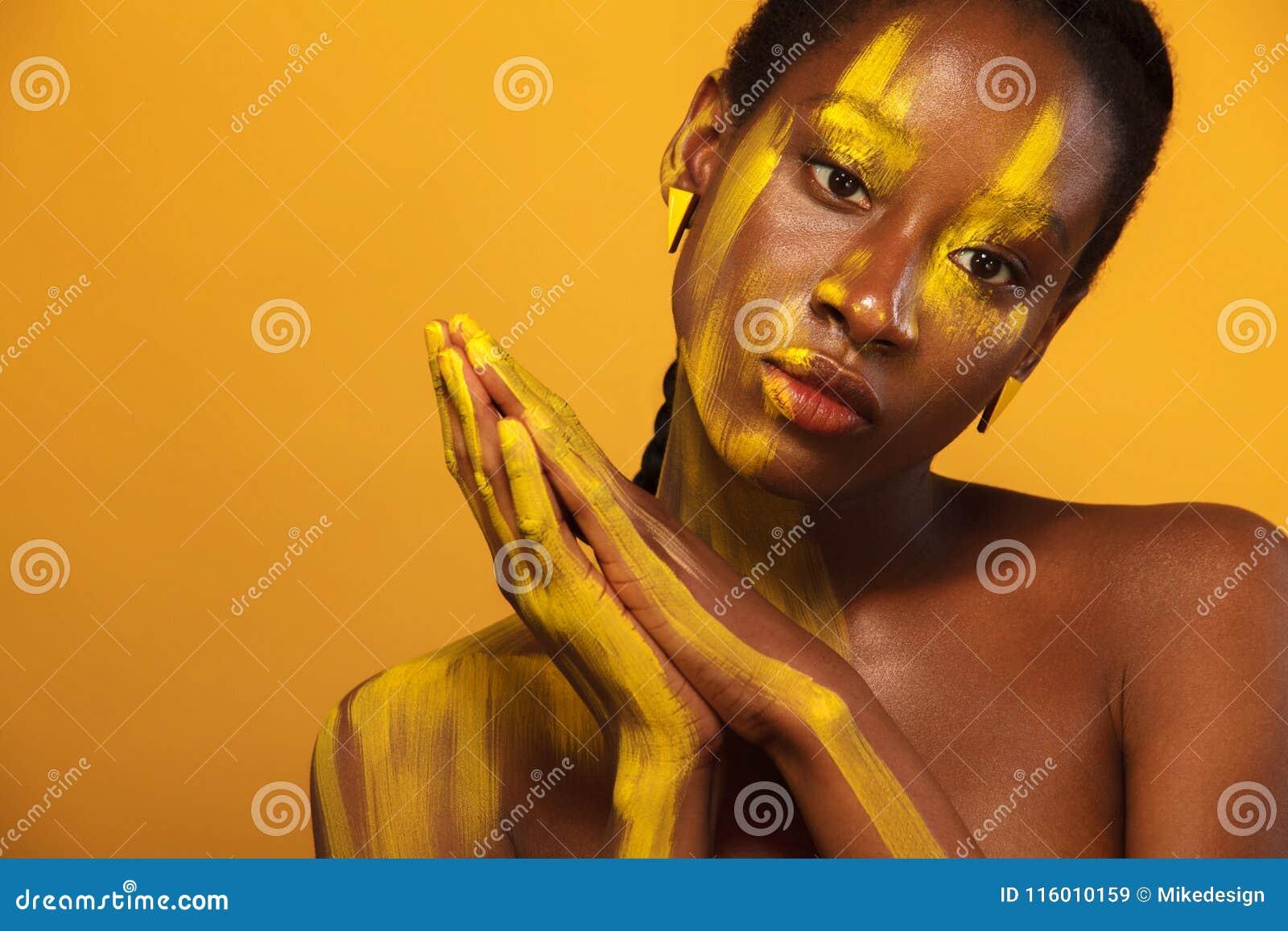 Jeune femme africaine gaie avec le maquillage jaune de ressort sur ses yeux Modèle femelle sur le fond jaune d été