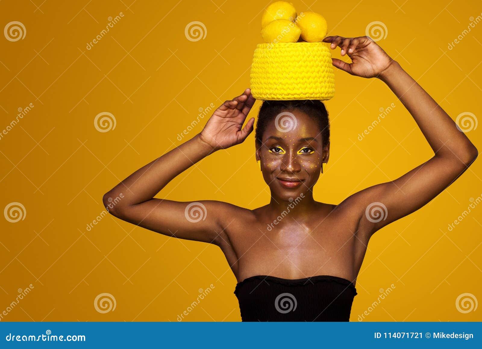 Jeune femme africaine gaie avec le maquillage jaune sur ses yeux Modèle femelle sur le fond jaune avec les citrons jaunes