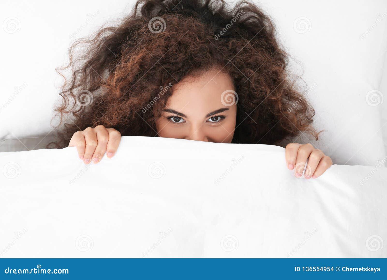 Jeune femme afro-américaine se trouvant sous la couverture bedtime