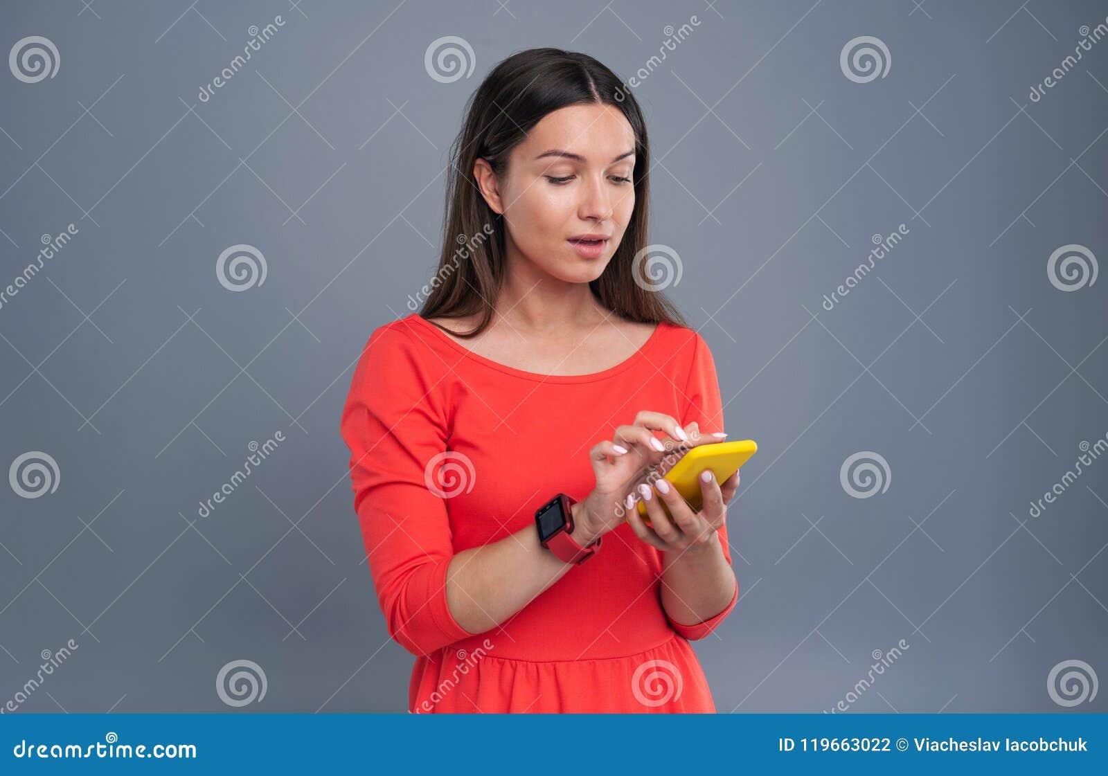 Jeune femme agréable introduisant un message textuel