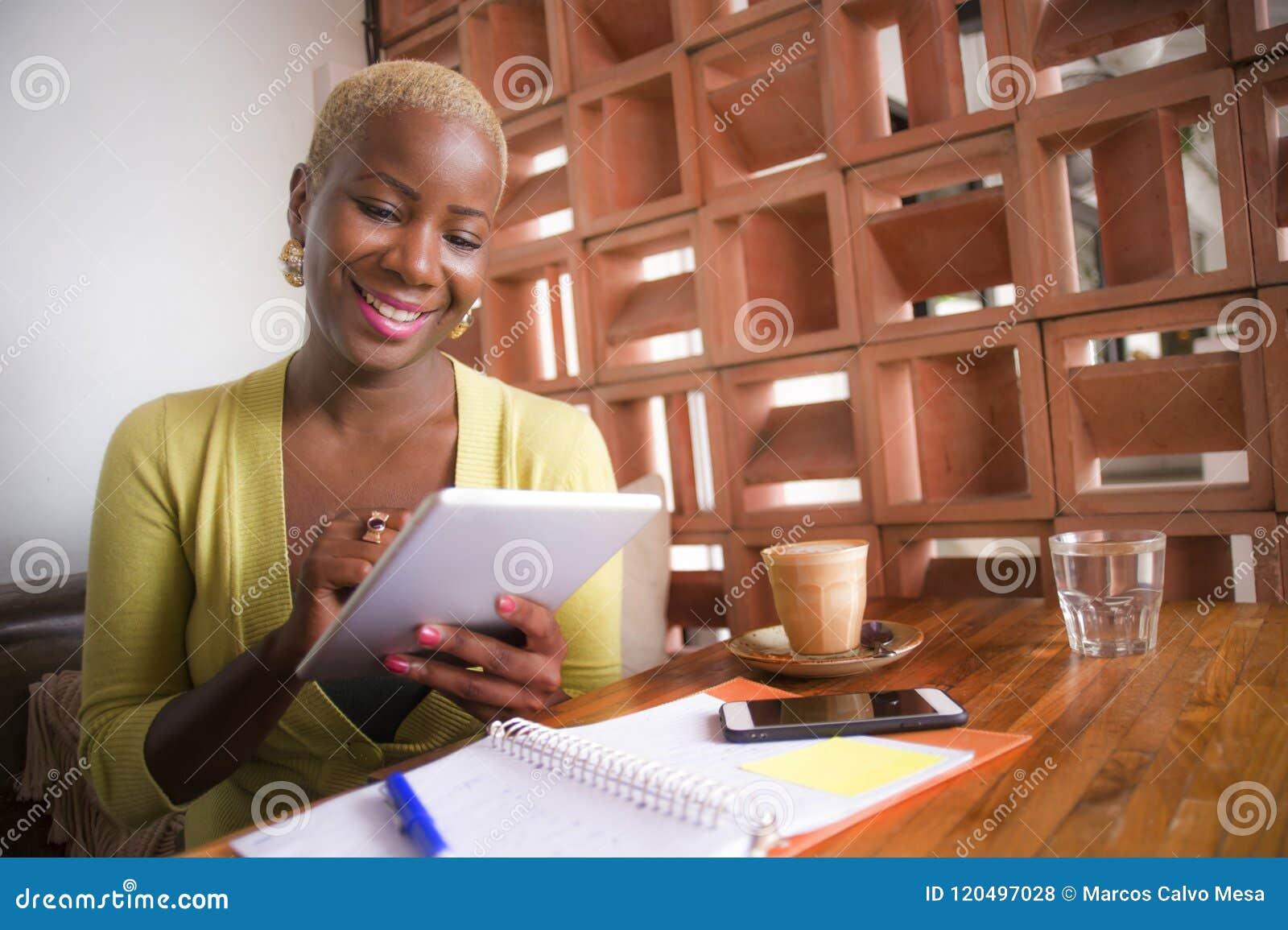 Jeune femme américaine d affaires d africain noir élégant et bel travaillant en ligne avec la protection numérique de comprimé au