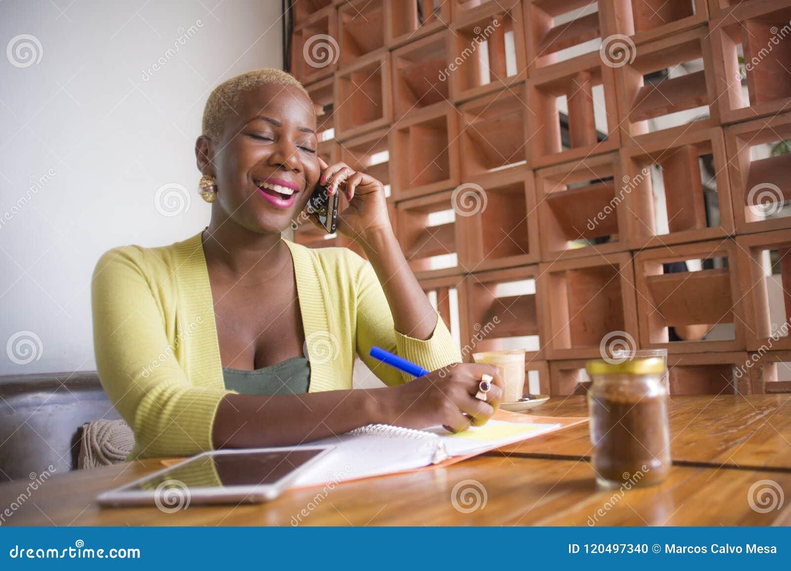 Jeune femme américaine d affaires d africain noir élégant et bel travaillant en ligne avec le téléphone portable au café prenant