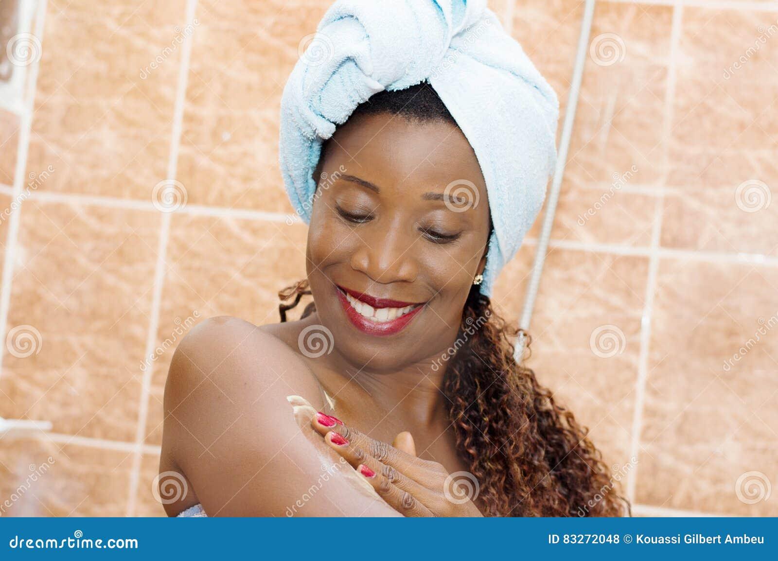 Jeune femme appliquant la lotion de corps après bain