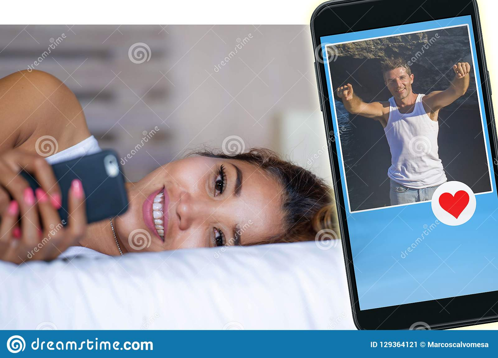 Jeune femme asiatique attirante et heureuse se trouvant sur le lit utilisant le media social APP dans le téléphone portable reche