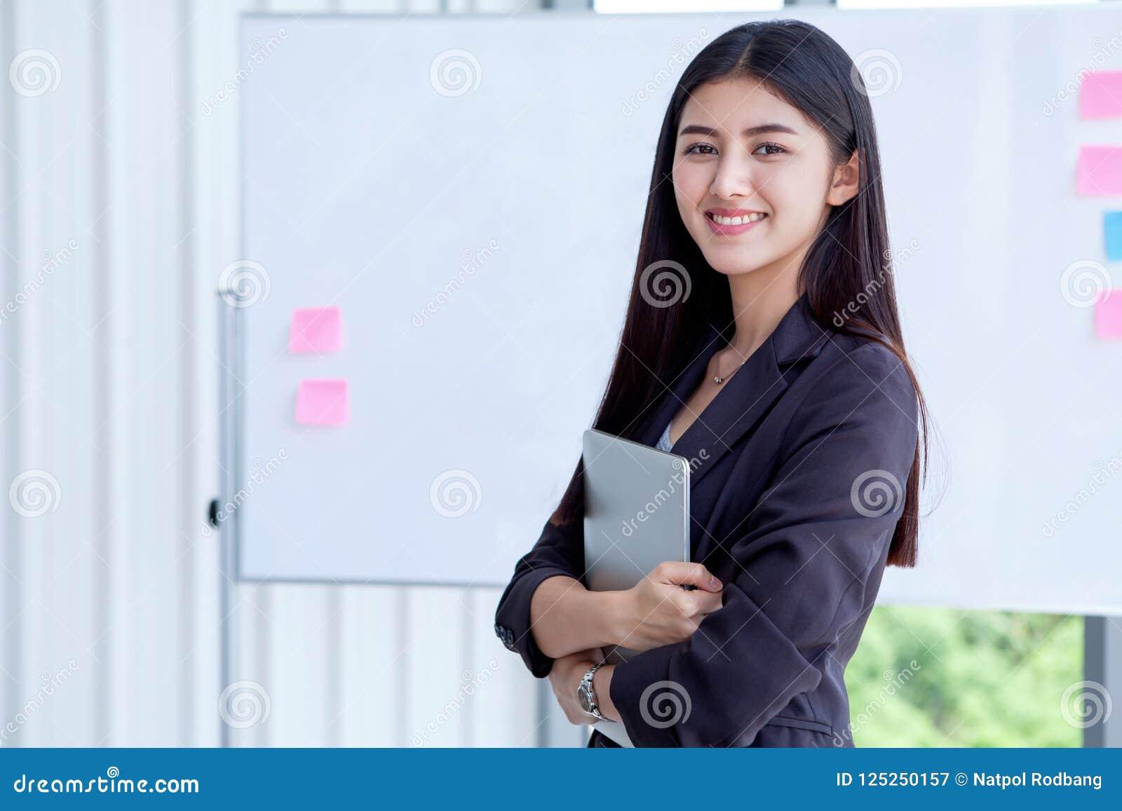 Jeune femme asiatique d affaires tenant l isola de tablette de Digital