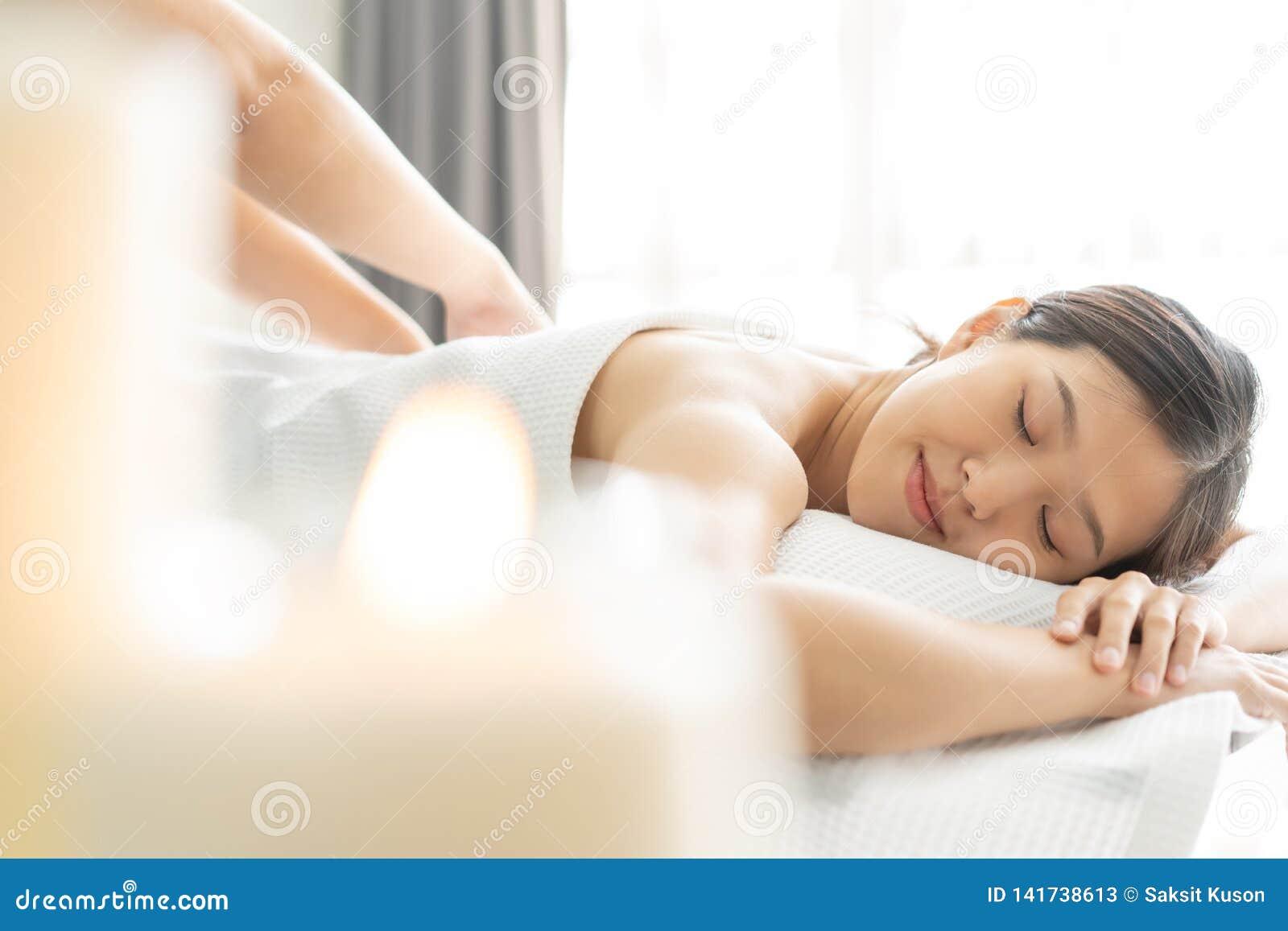 Jeune femme asiatique dans le salon de station thermale obtenant le massage