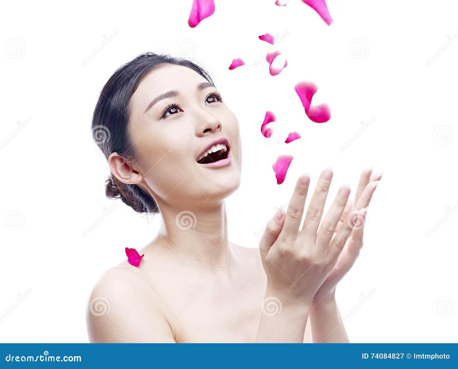 Jeune femme asiatique essayant d attraper les pétales en baisse