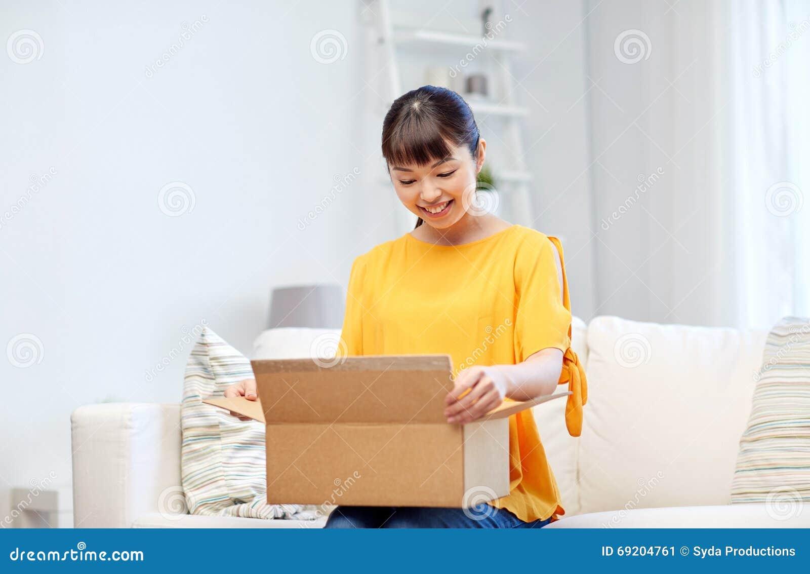 jeune femme asiatique heureuse avec la bo te de colis la maison photo stock image 69204761. Black Bedroom Furniture Sets. Home Design Ideas