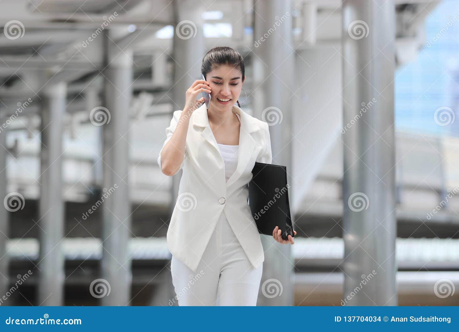 Jeune femme asiatique sûre d affaires parlant au téléphone pendant la marche au bureau