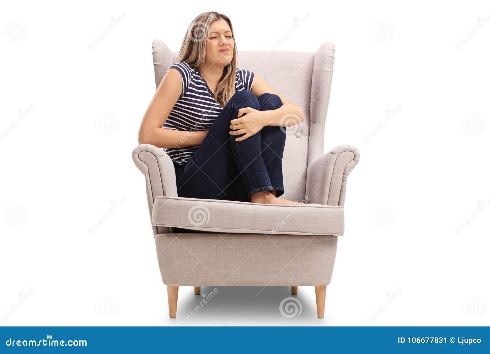 jeune femme assise dans un fauteuil ayant un mal d 39 estomac. Black Bedroom Furniture Sets. Home Design Ideas