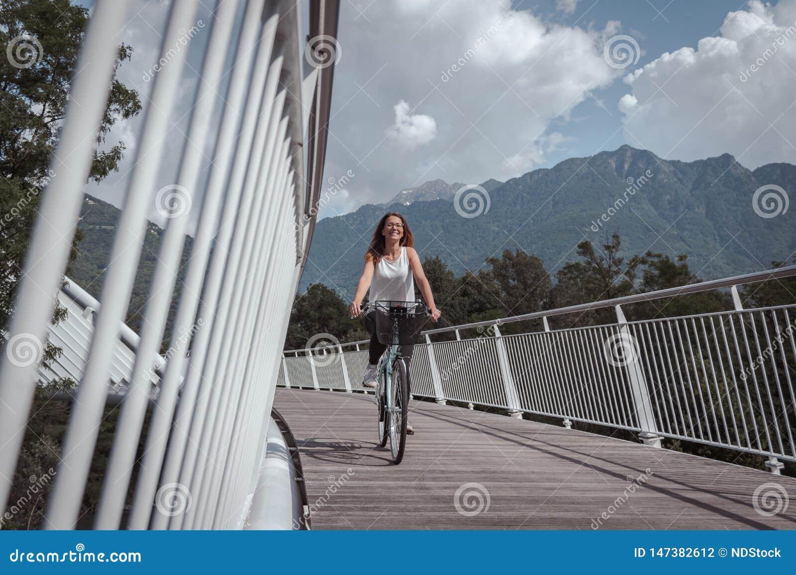 Jeune femme attirante avec la bicyclette sur un pont
