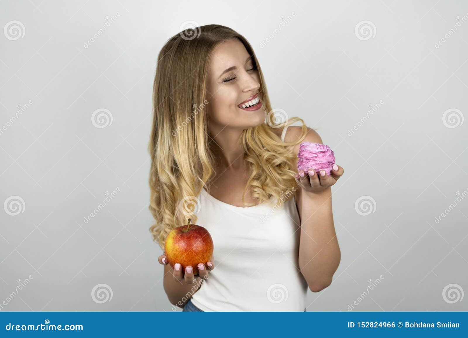 Jeune femme attirante blonde tenant la pomme rouge juteuse en une main et petit gâteau savoureux rose dans l autre blanc d isolem