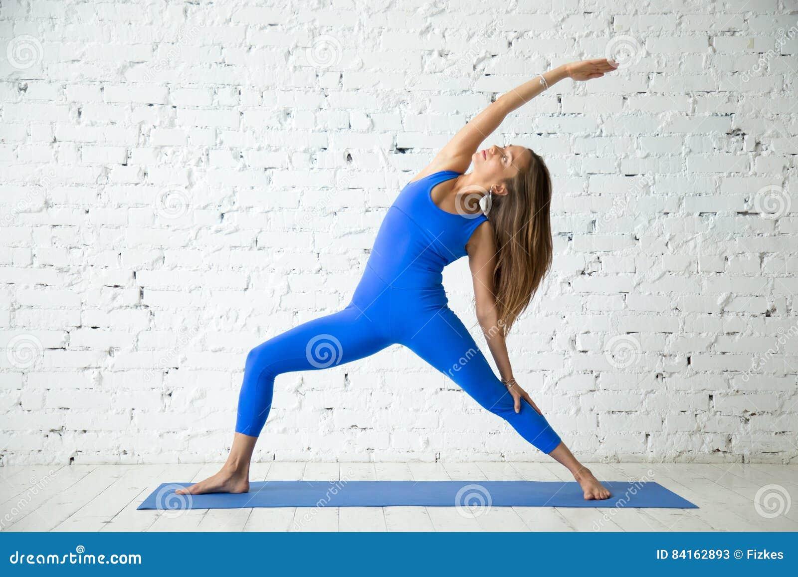 Jeune femme attirante dans la pose inverse de guerrier, CCB blanc de studio