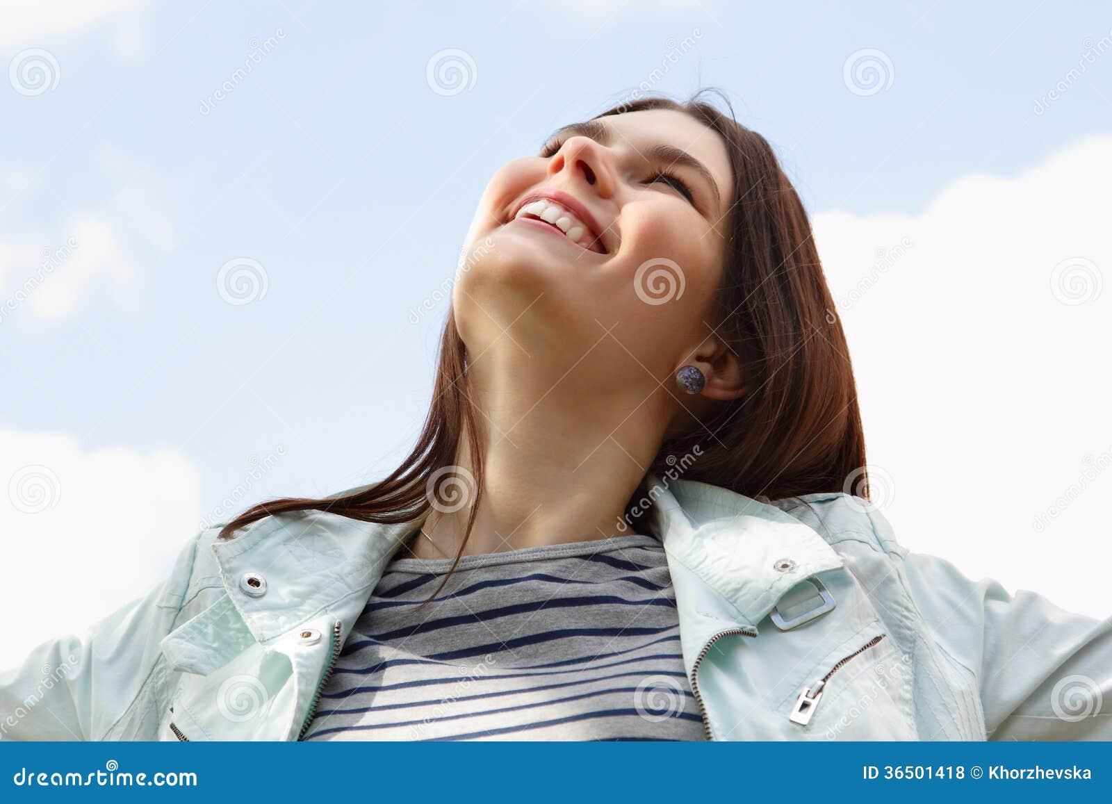Jeune femme attirante de sourire heureuse au-dessus de ciel bleu