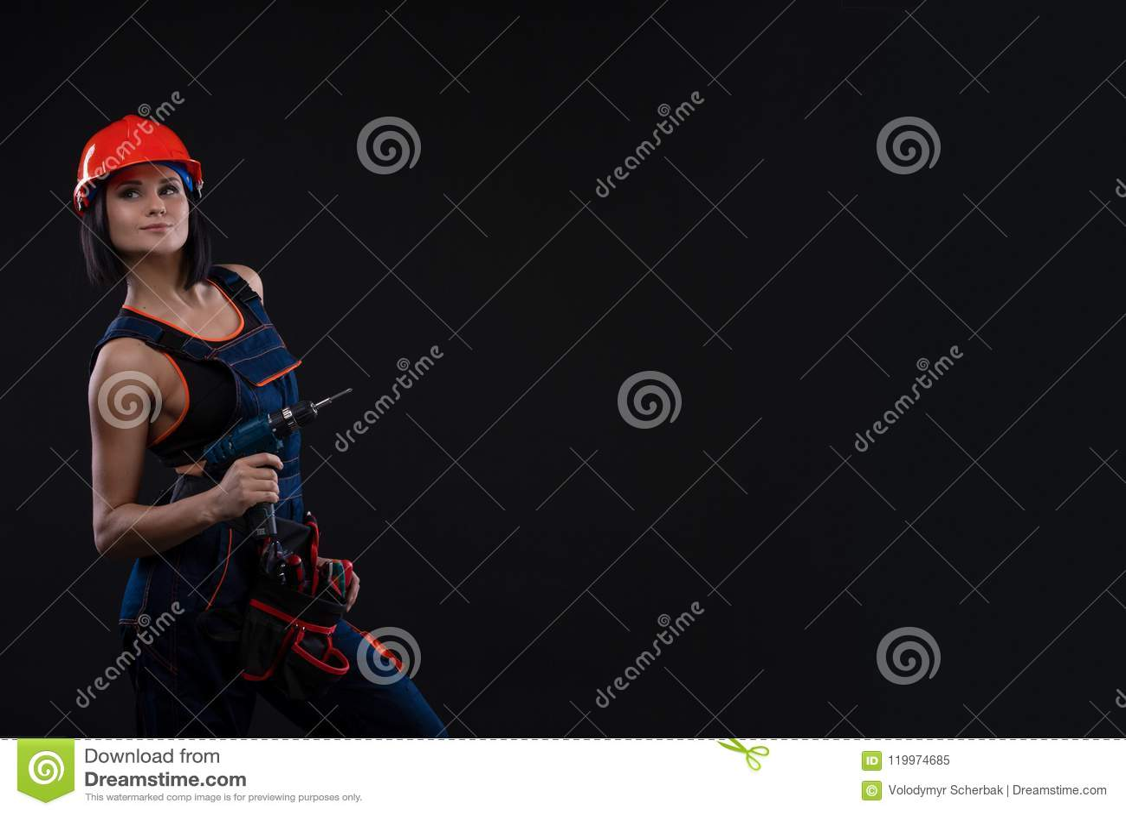 Jeune femme attirante faisant des réparations au fond noir Portrait d un travailleur de la construction féminin Bâtiment, concept