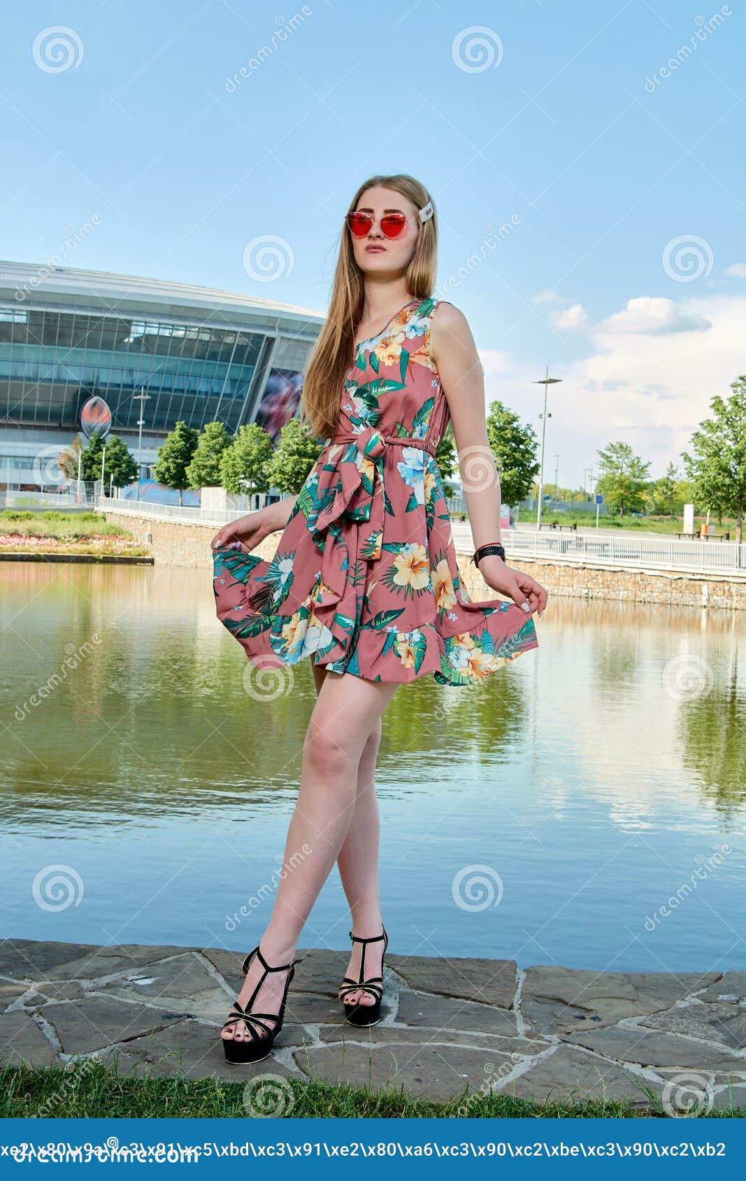 Jeune femme attirante Lunettes de soleil rouges, robe de couleur Portrait du ` s de fille Fond de stade de football